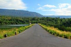 La strada allunga lungo un bello fiume o lago, con le montagne, il cielo blu, la nuvola bianca e le foreste verdi nella priorità  Fotografie Stock Libere da Diritti
