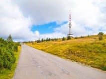 La strada asfaltata che conducono al trasmettitore della TV e l'allerta si elevano sulla sommità della montagna di Praded, Hruby  Fotografia Stock