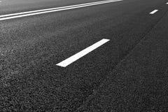 La strada asfaltata con la marcatura allinea le bande bianche Immagini Stock
