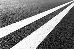La strada asfaltata con la marcatura allinea le bande bianche Fotografia Stock Libera da Diritti