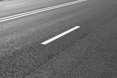 La strada asfaltata con la marcatura allinea le bande bianche Fotografia Stock