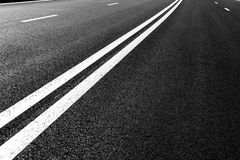 La strada asfaltata con la marcatura allinea le bande bianche Fotografie Stock Libere da Diritti