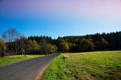 La strada asfaltata delle montagne del minerale metallifero che passa attraverso il prato fotografie stock