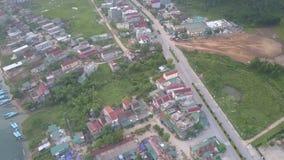 La strada asfaltata funziona lungo il villaggio vivace situato sulla sponda del fiume stock footage