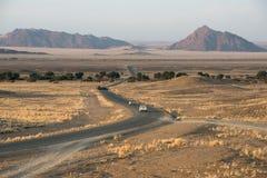La strada asfaltata moderna con le automobili sta piegando attraverso i campi namibiani Immagini Stock Libere da Diritti