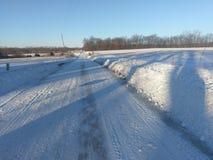 La strada campestre dopo lo spazzaneve ha aperto la strada dopo la bufera di neve fotografie stock libere da diritti