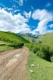 La strada con la gomma segue la conduzione alle montagne e Fotografia Stock