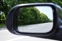 La strada con le marcature è riflessa nello specchio di vista laterale fotografia stock libera da diritti
