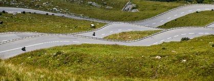 La strada curva come le onde nelle colline verdi delle alpi svizzere Immagine Stock Libera da Diritti
