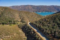 La strada del deserto conduce al bacino idrico blu fotografia stock libera da diritti
