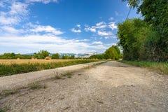 La strada del terreno coltivabile in un paesaggio della montagna con i campi ha riempito di ha Immagini Stock Libere da Diritti