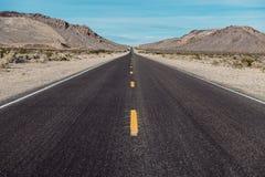 La strada diritta lunga scenica vuota del deserto con la marcatura gialla allinea Immagini Stock Libere da Diritti