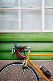 La strada gialla va in bicicletta il parcheggio contro la parete di legno verde Fotografia Stock