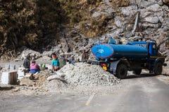La strada ha bloccato con i lavoratori ed il camion blu per la riparazione della strada nell'inverno vicino al modo al lago Tsomg fotografia stock libera da diritti