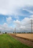 La strada lungo i giacimenti di grano, pali di potere Immagine Stock