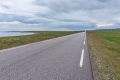 La strada mi allunga nella distanza su un fondo di verde Fotografia Stock