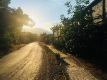 La strada nei raggi caldi del tramonto fotografia stock