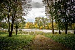 La strada nel parco che conduce al fiume in autunno Autunno Fotografia Stock Libera da Diritti