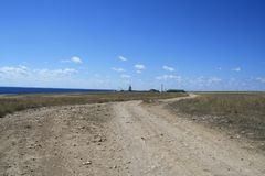 La strada nella steppa nell'ambito dello skyand del blu si appanna al mare Fotografia Stock Libera da Diritti