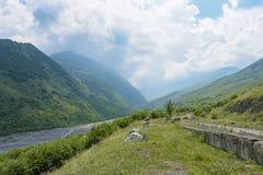 La strada nella vista di estate di Genaldon della gola e del fiume di Karmadon Ossetia del nord, Russia Le montagne di Caucaso fotografie stock