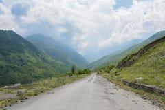 La strada nella vista di estate di Genaldon della gola e del fiume di Karmadon Ossetia del nord, Russia Le montagne di Caucaso immagini stock