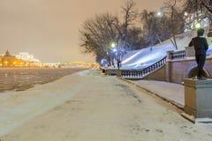 La strada nelle derive della neve vicino al fiume nel parco nella sera fotografia stock