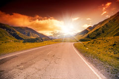 La strada nelle montagne abbellisce con il tramonto luminoso fotografie stock