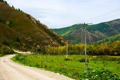 La strada non asfaltata che scompare nelle montagne serpeggia Fotografia Stock