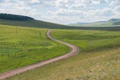 La strada non asfaltata rurale va oltre l'orizzonte lungo la steppa verde Fotografia Stock