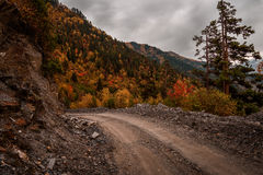 La strada non asfaltata sparsa con le rocce sui precedenti delle montagne Immagine Stock