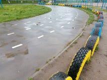 La strada pareggiante dell'asfalto bagnato gira a sinistra allo stadio della scuola Immagini Stock Libere da Diritti