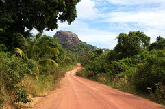 La strada polverosa che passa con il verde ha colorato i cespugli che conducono ad una grande roccia nera Fotografia Stock