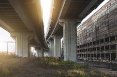 La strada principale ad alta velocità su massimo sostiene, vicino alla vecchia fabbrica, il magazzino Fotografia Stock