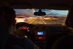 La strada principale di notte dall'interno dell'automobile con moto ha offuscato l'accelerazione fotografia stock