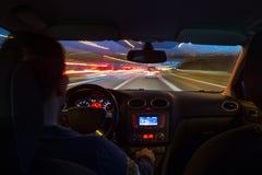 La strada principale di notte dall'interno dell'automobile con moto ha offuscato l'accelerazione immagini stock