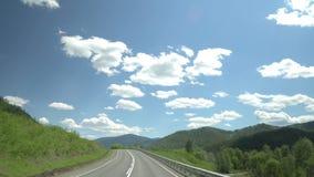 La strada principale nella zona di montagna Movimento della macchina fotografica 4K Cielo e nubi stock footage