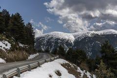 La strada principale in spagna per attraversare i Pirenei nevicati in una luce del giorno parzialmente nuvolosa con alcuni alberi Fotografia Stock