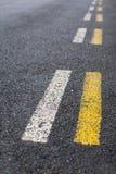 La strada tratteggiata parallela allinea nel bianco e nel giallo Fotografia Stock Libera da Diritti