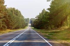 La strada vuota che retrocede nella distanza, si trasforma in in un punto sull'orizzonte fotografia stock