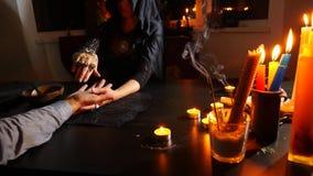 La strega è un indovino con il primo piano delle candele Un rituale magico divination Halloween, 4k, rallentatore stock footage