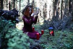 La strega dai capelli rossi tiene un rituale con una sfera di cristallo Fotografia Stock Libera da Diritti