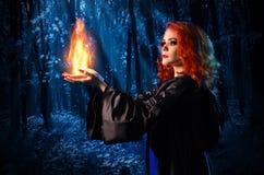 La strega nella foresta di notte tiene il fuoco fotografia stock