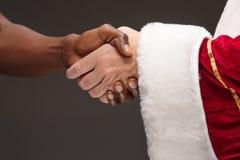 La stretta di mano della mano di Santa Claus e della mano dell'uomo africano Fotografie Stock Libere da Diritti