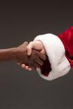 La stretta di mano della mano di Santa Claus e della mano dell'uomo africano Fotografie Stock