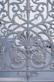 La struttura della griglia in ferro battuto sulla finestra fine Pezzo fucinato artistico Fotografia Stock