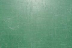 La struttura della superficie del consiglio scolastico verde è coperta di molti graffi da scrittura con il gesso Fotografia Stock