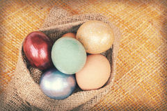 La struttura di carta d'annata, uova di Pasqua variopinte in sacco insacca su tessuto Fotografie Stock