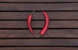 La struttura di legno scura con i peperoncini rossi Immagini Stock
