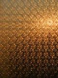 La struttura di una finestra di vetro glassata attraverso cui il sol levante splende ha un colore di dorato-Brown immagini stock libere da diritti