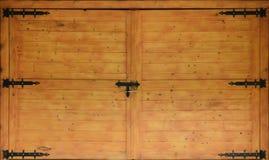 La struttura di vecchi portoni di legno, vecchio fatto di giallo ha trattato il legno con la cerniera di porta del nero del metal immagine stock